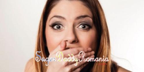 O fată drăguță surprinsă, cu mâna în gură